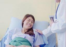 Mulher deitada em maca de internação hospitalar